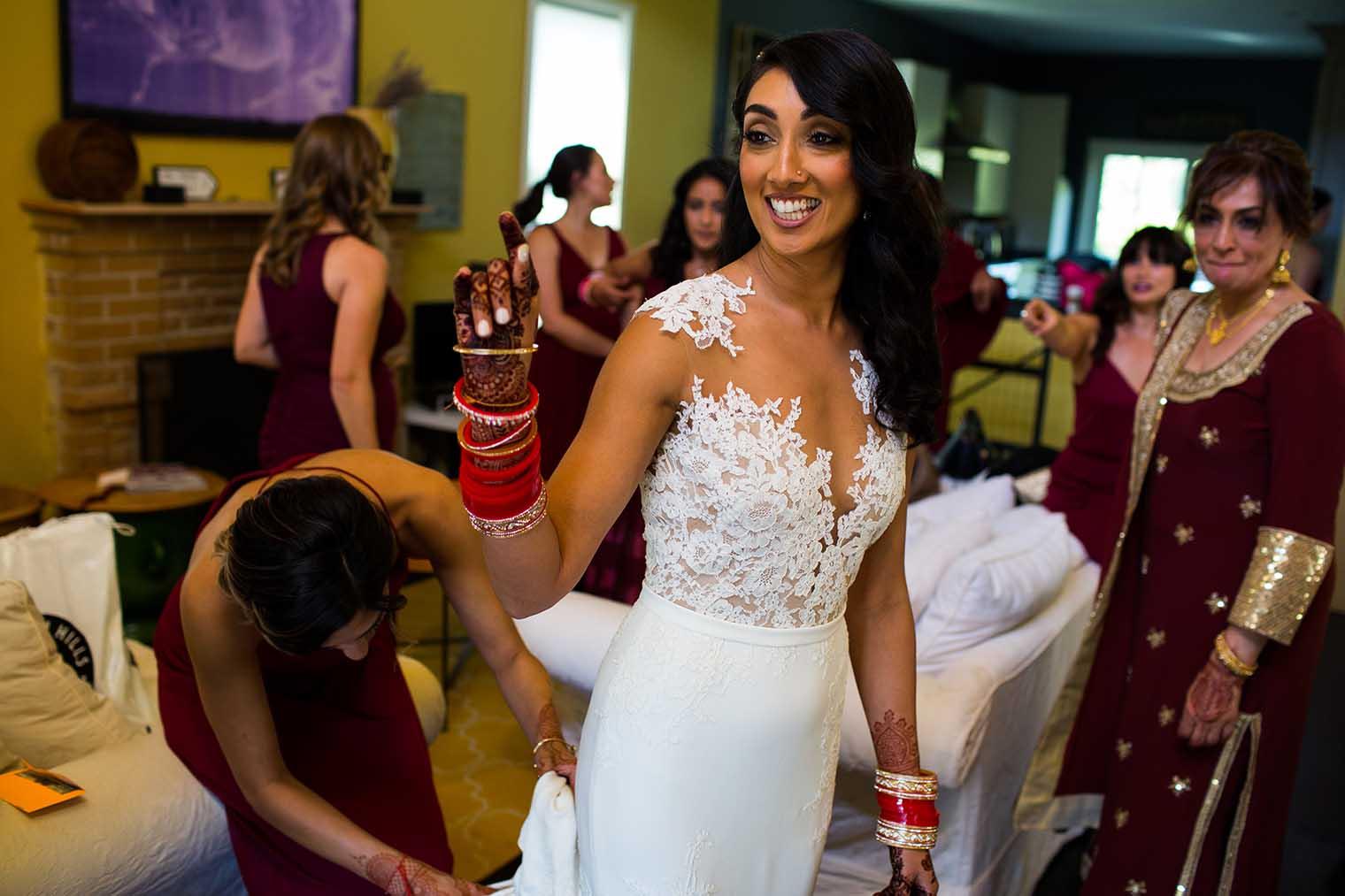 Bride putting on dress in Napa California