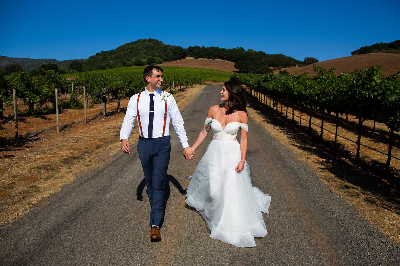 Bride and groom walking through winery