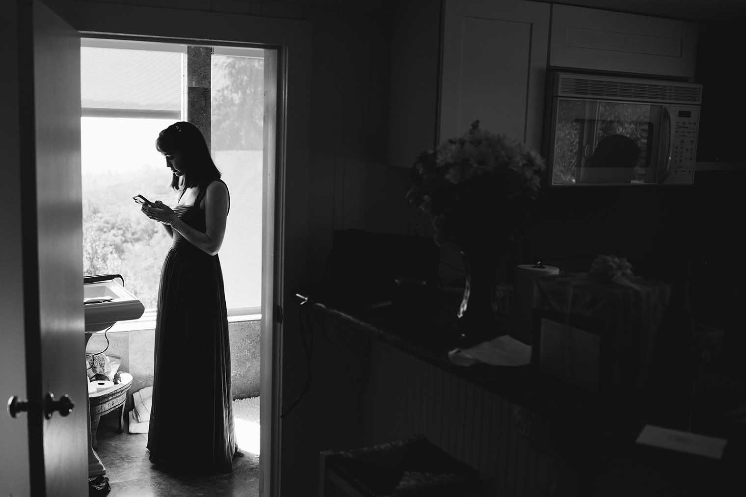 Bridesmaid texting during the getting ready